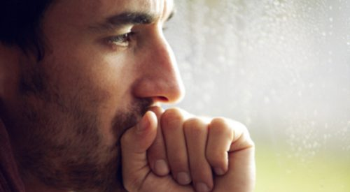 A young looking pensive while covering his mouth with a clenched hand
